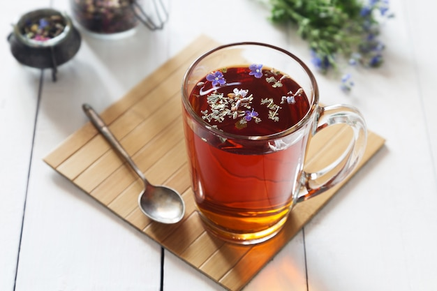 Herbal tea with flowers in transparent glass Premium Photo