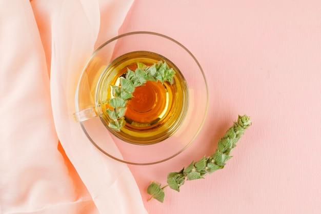 ピンクとテキスタイルのガラスカップでハーブとハーブティー、フラットレイアウト。 無料写真