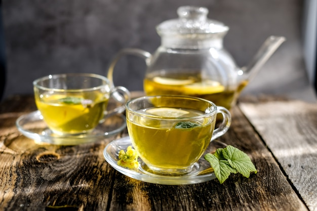 Herbal tea with lemon and honey in glass cup and teapot Premium Photo