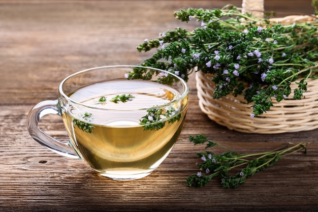 Herbal tea with thyme over rustic wooden background. Premium Photo