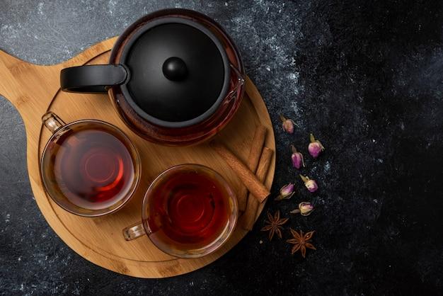 Травяной зимний чай в чашках со специями на деревянной доске. Бесплатные Фотографии