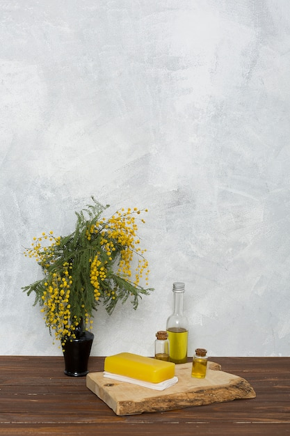 Herbal yellow soap on folded napkin and essential oil bottle near the yellow mimosa flower vase Free Photo