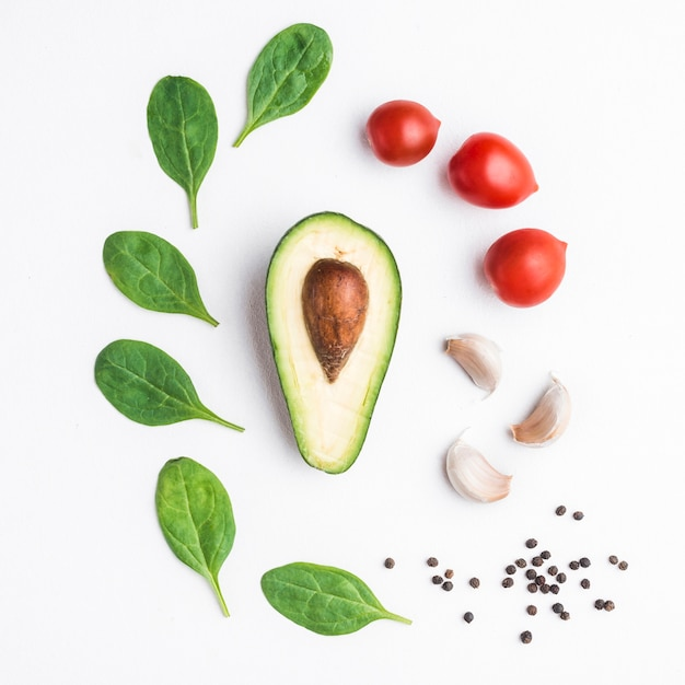 Herbs and vegetables around avocado Free Photo