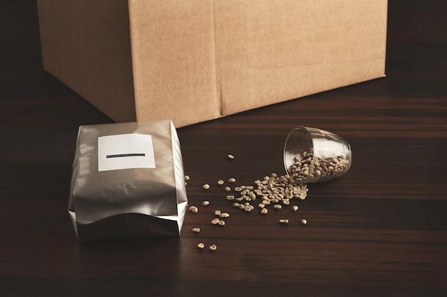 갓 구운 볶은 커피로 가득 찬 밀폐형 실버 패키지로 타락한 투명 컵 근처의 붉은 나무 테이블에 향기를 보존하고 생 녹색 껍질을 벗긴 커피 원두와 판지 상자 무료 사진