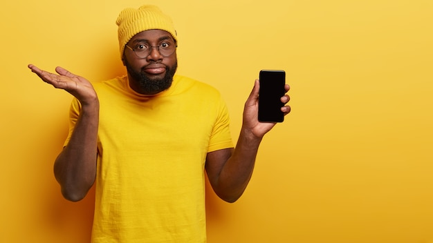 Hesitant confused man choose new smart phone, holds modern electronic device with mock up screen, raises palm doubtfully, hesitates whether to buy, wears bright fashionable yellow hat and t shirt Free Photo