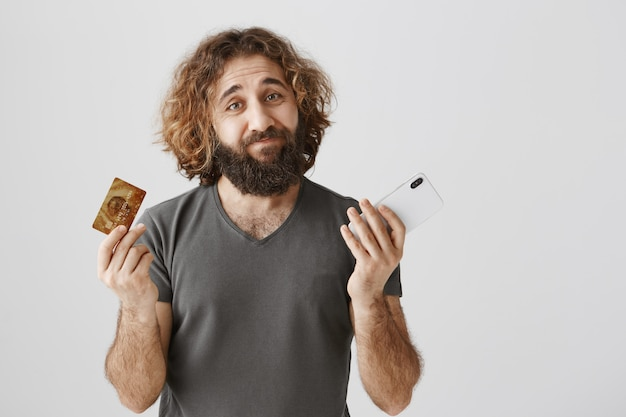 Нерешительный мужчина с ближнего востока с кредитной картой и мобильным телефоном, невежественно пожимая плечами Бесплатные Фотографии