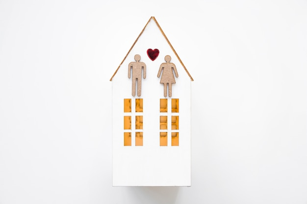 Heterosexual couple on toy house Free Photo