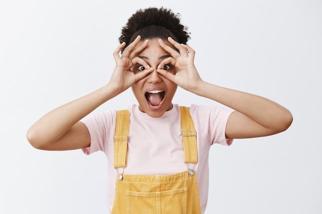 Ehi, ti vedo. ragazza felice emotiva giocosa che scherza in tuta gialla sopra la maglietta, fa cerchi con le mani e guarda attraverso di essa stupita come se usasse un binocolo o occhiali Foto Gratuite