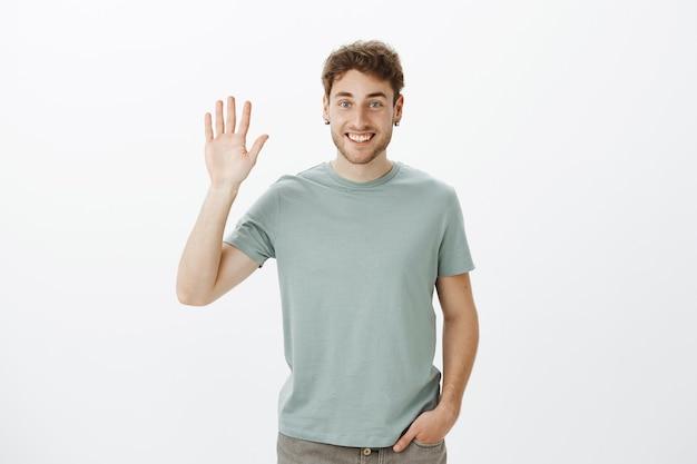 はじめまして。手を上げるとこんにちはジェスチャーで手のひらを振ってカジュアルなtシャツでハンサムな発信ヨーロッパ男の肖像 無料写真