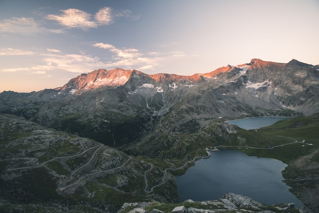 High altitude alpine lake, dams and water basins in idyllic land with majestic rocky mountain peaks glowing at sunset. wide angle view on the alps. Premium Photo