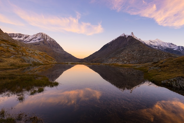 High altitude alpine lake in idyllic land with reflection of majestic rocky mountain Premium Photo