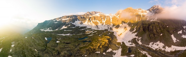 High altitude alpine landscape with majestic rocky mountain peaks. aerial panorama at sunrise. alps, andes, himalaya Premium Photo