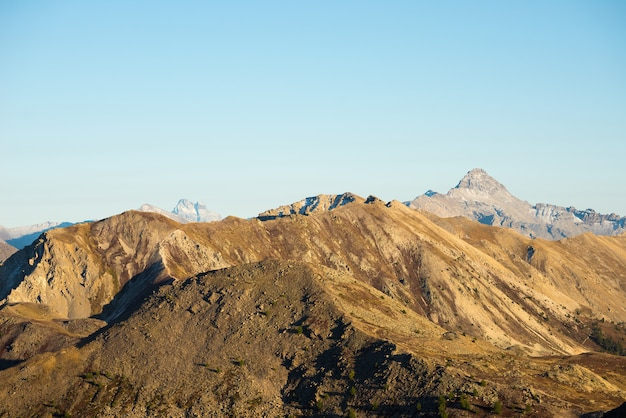 High altitude pasture, rocky mountain peaks and jagged ridge, with scenic sky, the italian alps. expansive view in backlight. toned desaturated image. Premium Photo