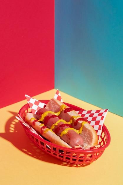 Композиция под большим углом с вкусным хот-догом и корзиной Бесплатные Фотографии