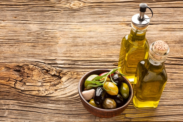 High angle assortment of colorful olives with oil bottle and copy space Free Photo