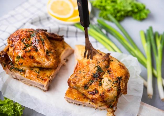 높은 각도로 구운 닭고기 반쪽을 샐러드와 함께 프리미엄 사진