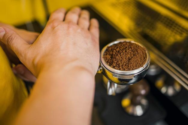 Angolo alto del barista che livella il livello del caffè per la tazza della macchina Foto Gratuite