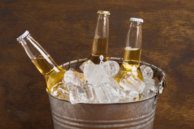 High angle beer bottles in ice cube bucket Free Photo