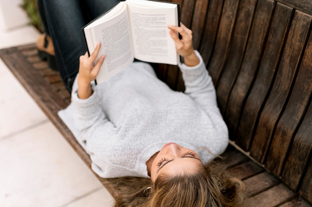 High angle blonde woman reading on a bench Free Photo