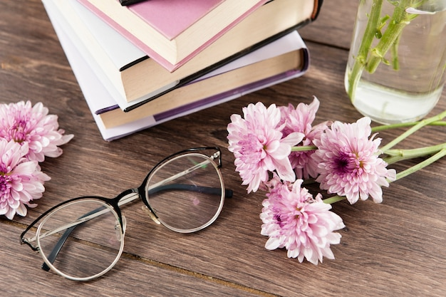 High angle of books flowers and glasses on wooden table Free Photo