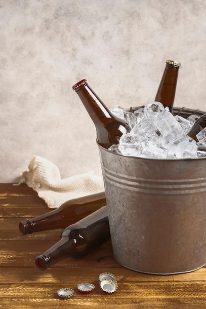 Высокий угол бутылки пива на столе и внутри ведро со льдом Бесплатные Фотографии