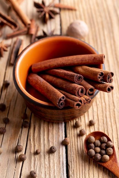 High angle of bowl with cinnamon sticks and nutmeg Free Photo