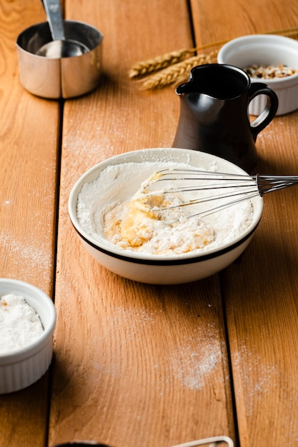 High angle of a bowl with whisk on wooden table Free Photo