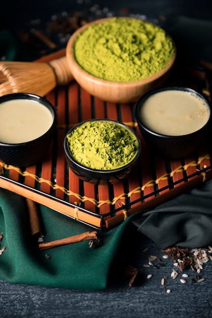 High angle bowls with green tea powder and tea drink Free Photo