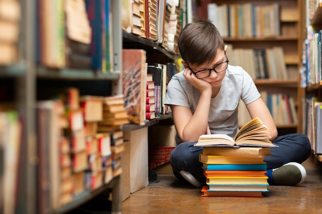 High angle boy at library reading Free Photo