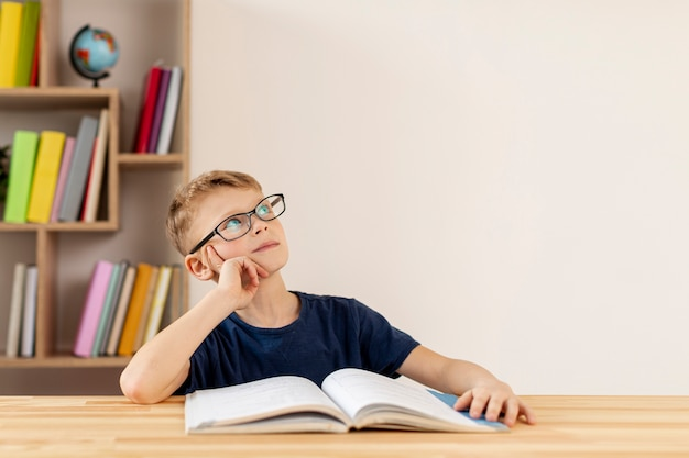 High angle boy thinking of the book read Free Photo