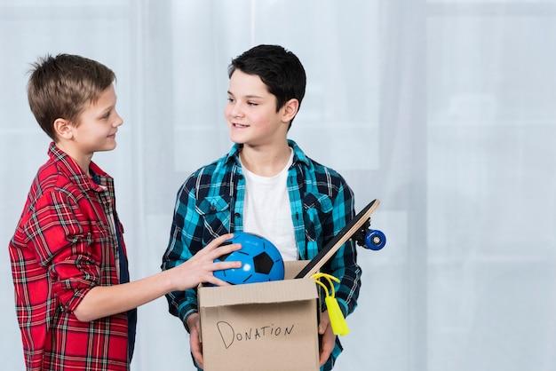 High angle boys holding donation box Free Photo