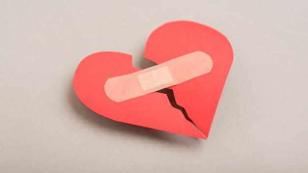 High angle broken heart with band-aid Premium Photo