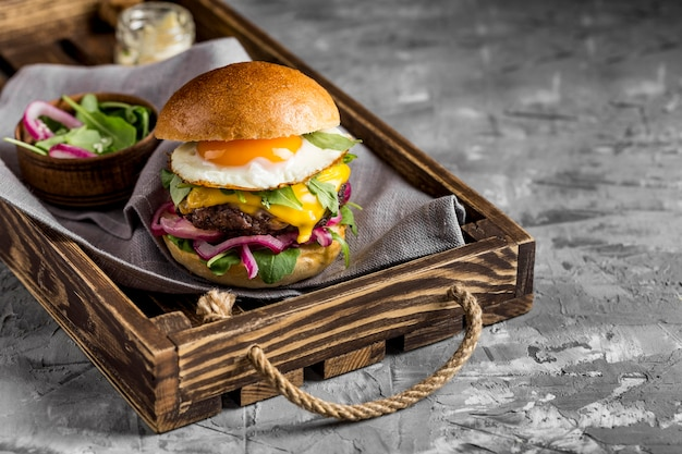 High angle cheeseburger with fried egg on tray Free Photo