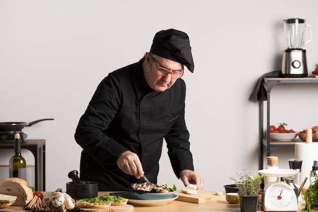 Cuoco unico dell'angolo alto che prepara insalata Foto Gratuite