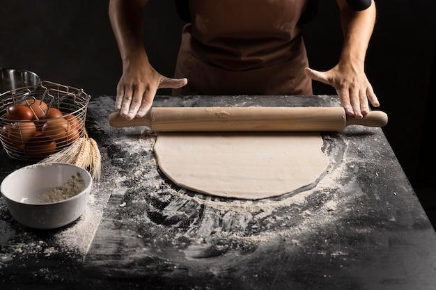 Alto angolo dello chef che rotola la pasta con la farina Foto Gratuite
