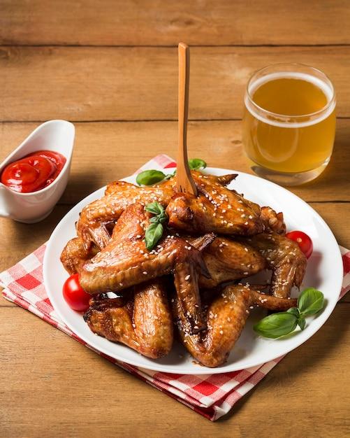 Куриные крылышки под большим углом на тарелке с кунжутом и кетчупом Бесплатные Фотографии