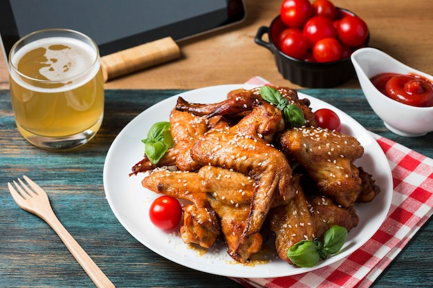 High angle chicken wings on plate with cherry tomatoes Free Photo