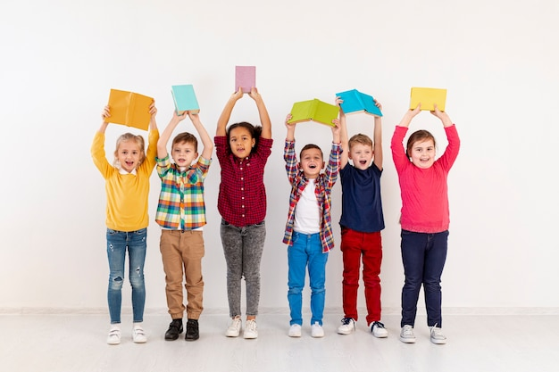 High angle childrens holding books above heads Free Photo