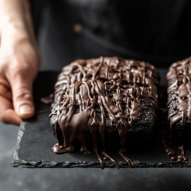 Alto angolo di torta al cioccolato tenuto dal pasticcere Foto Gratuite