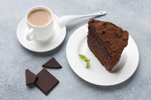 High angle of chocolate cake slice on plate with coffee Free Photo