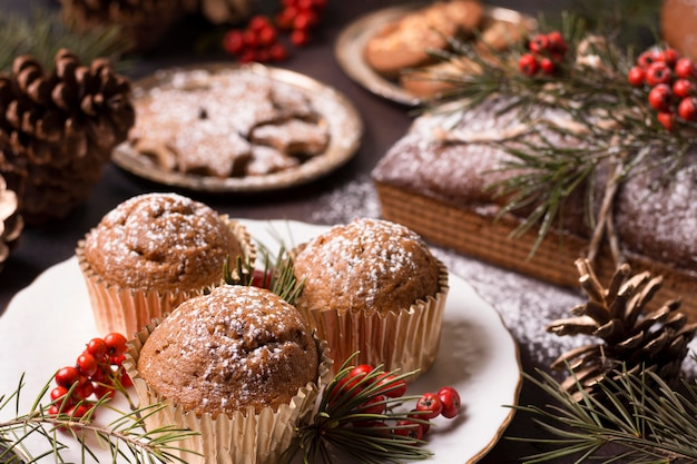 Alto angolo di cupcakes di natale con biscotti e pigne Foto Gratuite