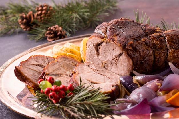 Alto angolo di bistecca di natale sulla piastra con pigne Foto Gratuite