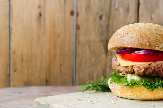 High angle close-up of burger on wooden board Free Photo