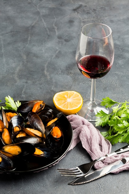 High angle close-up cooked mussels and wine bottle Free Photo