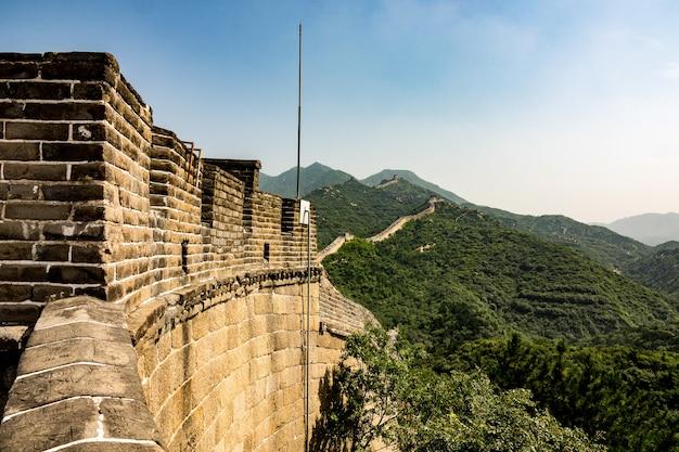 Colpo del primo piano dell'angolo alto della famosa grande muraglia cinese circondata da alberi verdi in estate Foto Gratuite