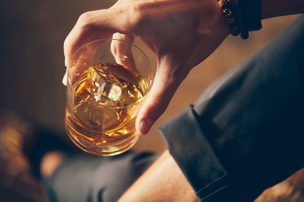 High angle closeup shot of a male holding a glass of whiskey Free Photo