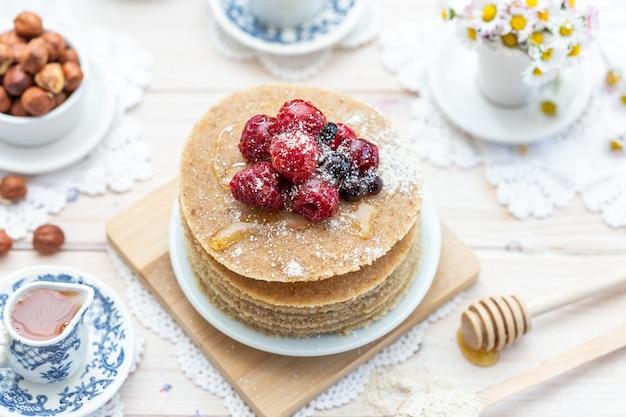 Крупным планом снимок сырых веганских блинов с медом и ягодами под высоким углом Бесплатные Фотографии