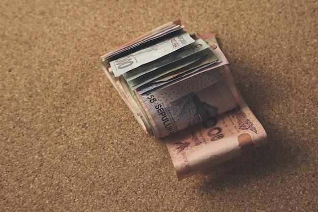 Elevato angolo di visione del primo piano di denaro contante su uno sfondo marrone Foto Gratuite