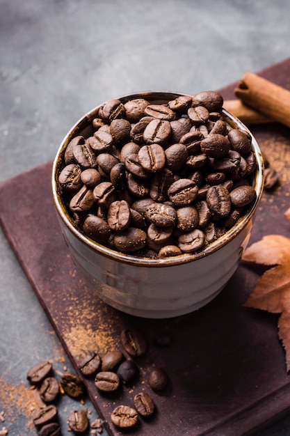 High angle coffee beans in cup on cutting board with cinnamon Premium Photo
