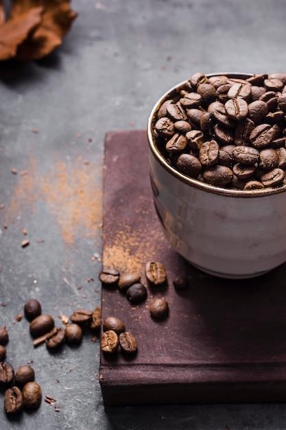 Chicchi di caffè ad alto angolo in tazza sul tagliere Foto Gratuite